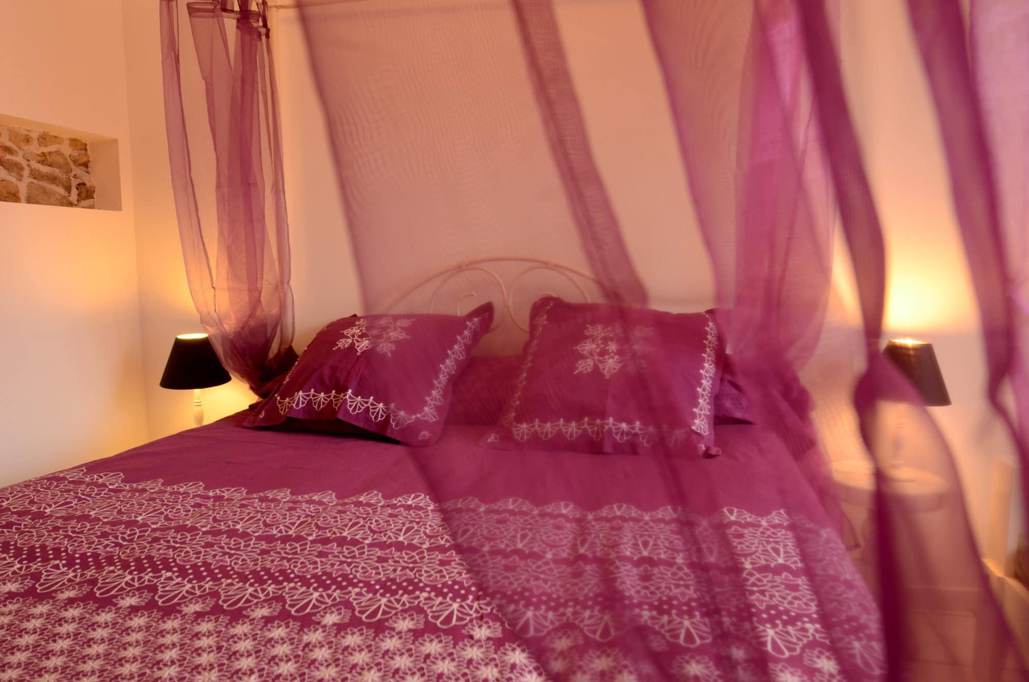 Chambre du gîte avec lit à baldaquin et voilage