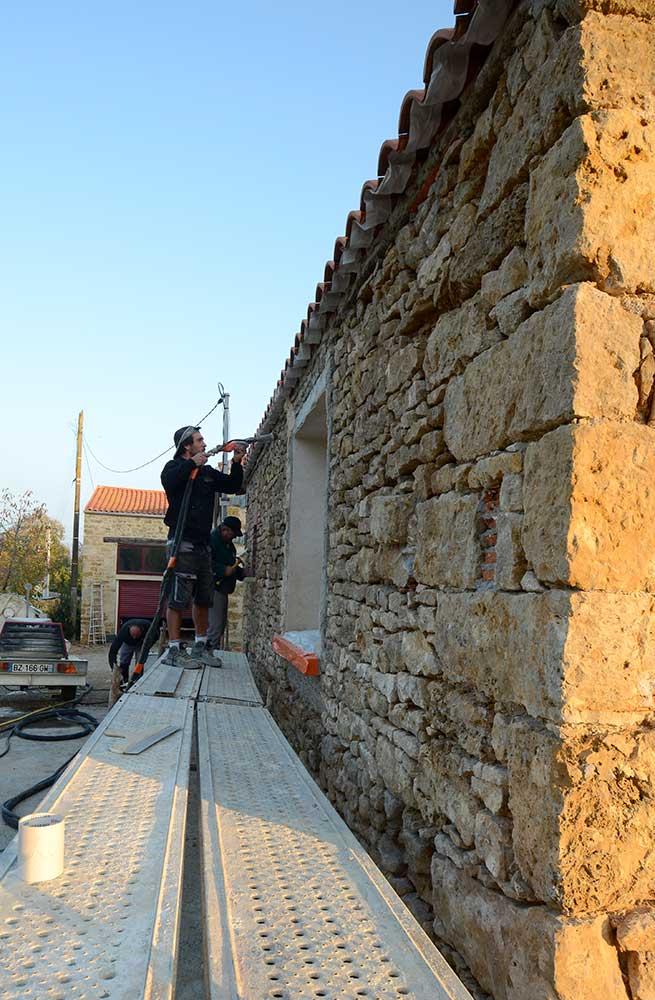 Maçon en train d'enduire le mur de moellon